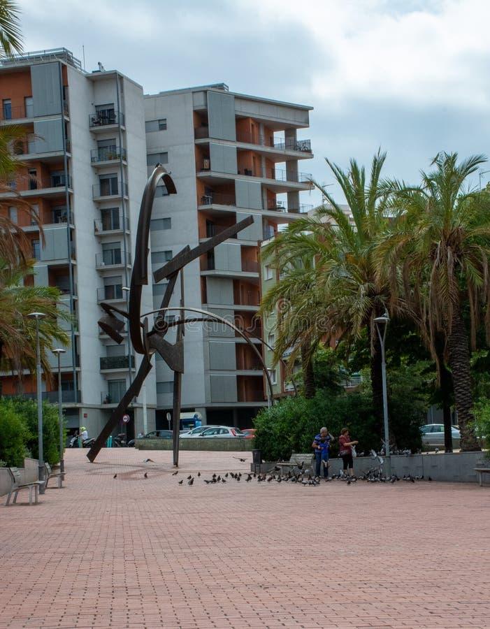 Οικογένεια που παίζει και που ταΐζει pidgeons δίπλα στο γλυπτό στη Βαρκελώνη στοκ εικόνα