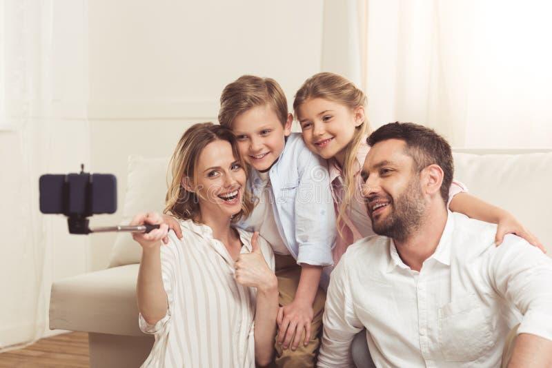 Οικογένεια που παίρνει selfie στο smartphone με το monopod στο σπίτι στοκ εικόνες με δικαίωμα ελεύθερης χρήσης