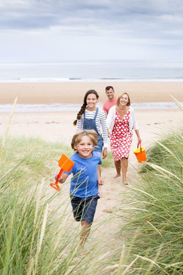 Οικογένεια που περπατά επάνω τους αμμόλοφους άμμου στοκ φωτογραφίες με δικαίωμα ελεύθερης χρήσης