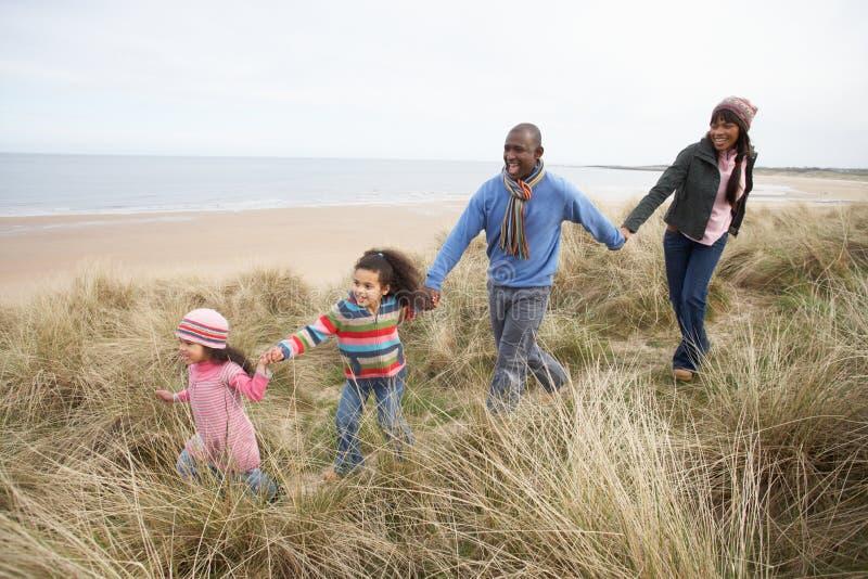 Οικογένεια που περπατά κατά μήκος των αμμόλοφων στη χειμερινή παραλία στοκ φωτογραφίες