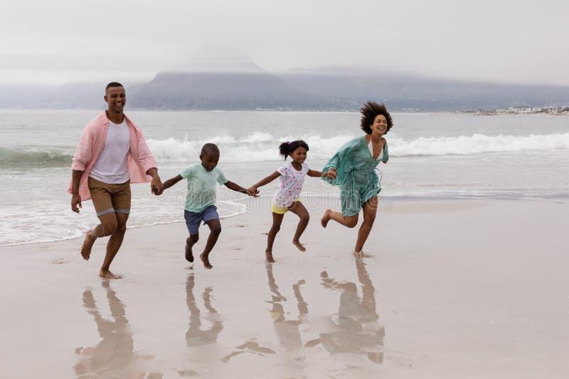 Οικογένεια που περπατά μαζί χέρι-χέρι στην παραλία στοκ φωτογραφίες