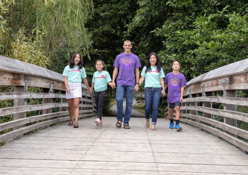 Οικογένεια που περπατά χέρι-χέρι στην ξύλινη γέφυρα στο δενδρολογικό κήπο πάρκων της Ουάσιγκτον, Σιάτλ, Ουάσιγκτον στοκ εικόνες