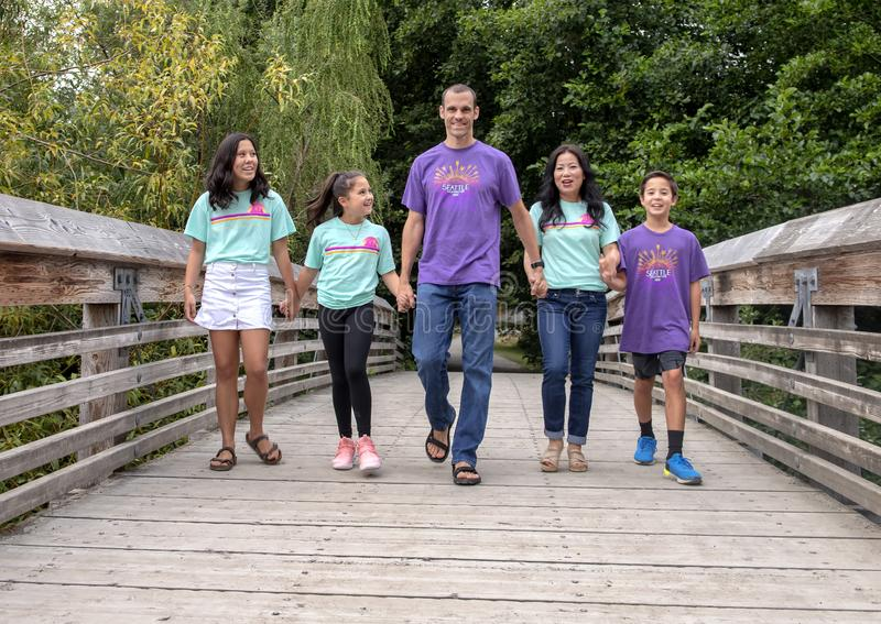 Οικογένεια που περπατά χέρι-χέρι στην ξύλινη γέφυρα στο δενδρολογικό κήπο πάρκων της Ουάσιγκτον, Σιάτλ, Ουάσιγκτον στοκ εικόνα