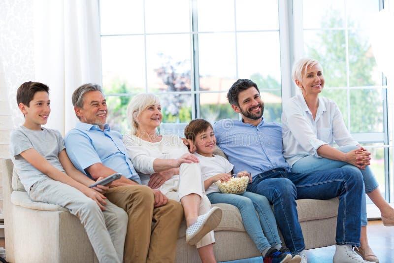 Οικογένεια που προσέχει τη TV στον καναπέ στοκ εικόνες