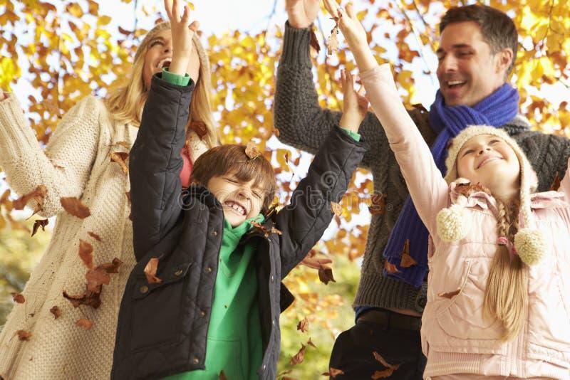 Οικογένεια που ρίχνει τα φύλλα στον κήπο φθινοπώρου στοκ εικόνα