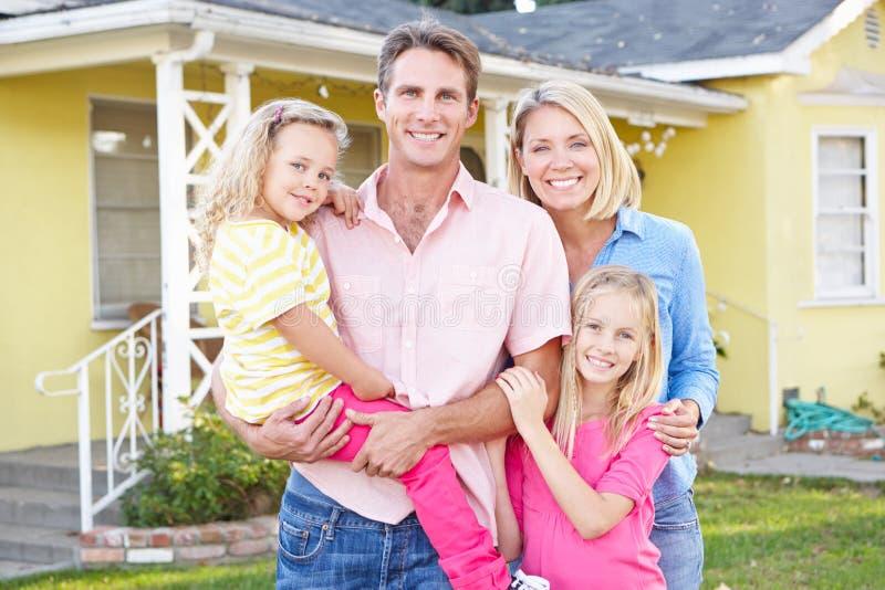 Οικογένεια που στέκεται έξω από το προαστιακό σπίτι στοκ εικόνα με δικαίωμα ελεύθερης χρήσης