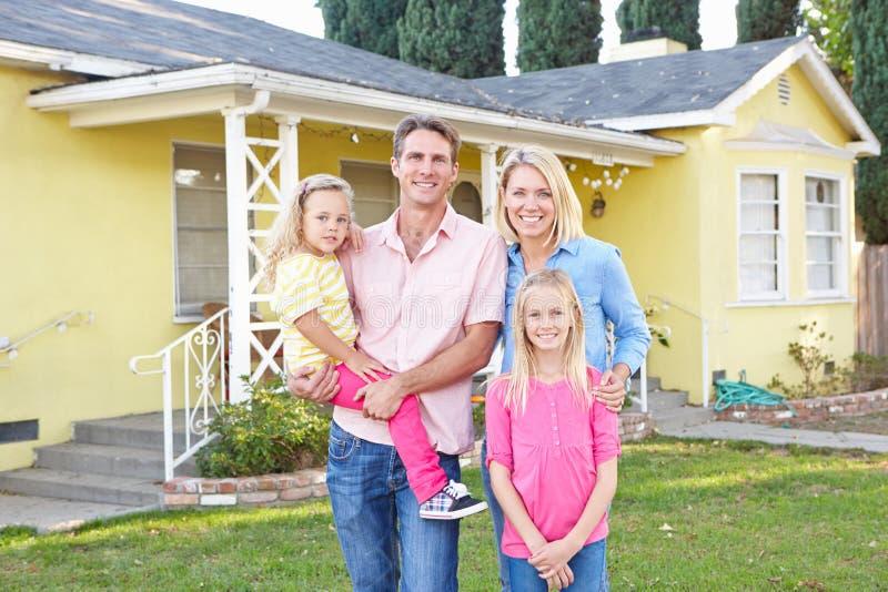 Οικογένεια που στέκεται έξω από το προαστιακό σπίτι στοκ εικόνες
