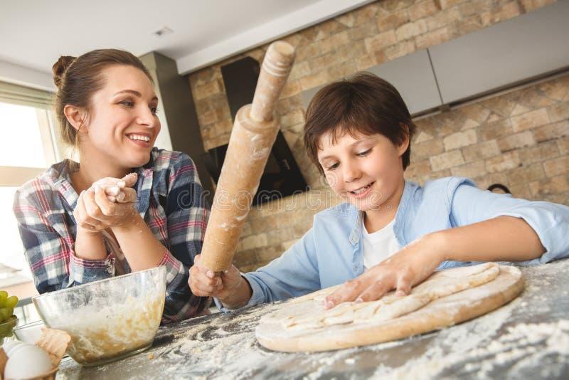 Οικογένεια που στέκεται στο σπίτι στον πίνακα στη μητέρα κουζινών μαζί που εξετάζει υπερήφανη τη βοήθεια γιων που κάνει την κινημ στοκ φωτογραφία με δικαίωμα ελεύθερης χρήσης