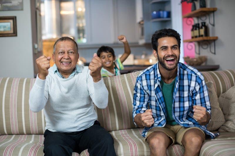 Οικογένεια που σφίγγει την πυγμή προσέχοντας τον αγώνα ποδοσφαίρου στοκ εικόνες