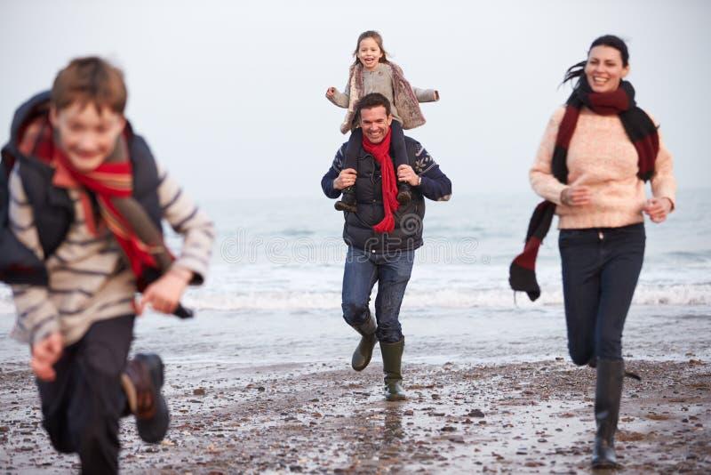 Οικογένεια που τρέχει κατά μήκος της χειμερινής παραλίας στοκ εικόνα