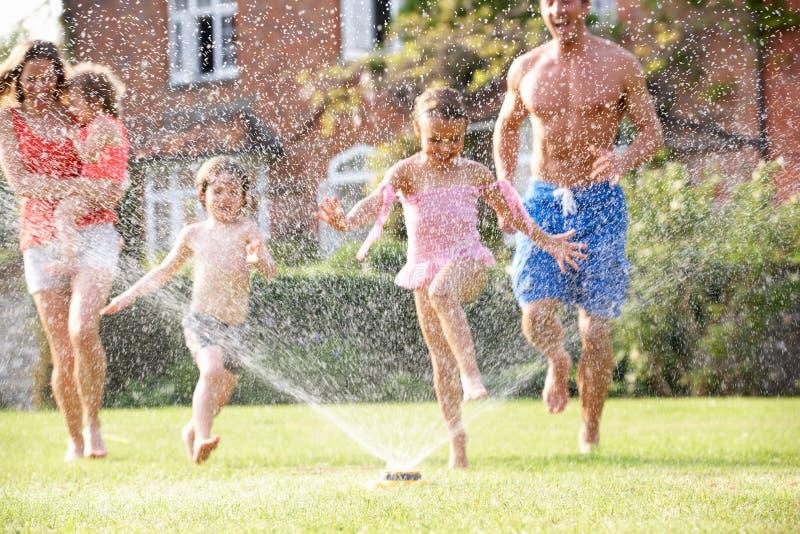 Οικογένεια που τρέχει μέσω του ψεκαστήρα κήπων στοκ εικόνες με δικαίωμα ελεύθερης χρήσης