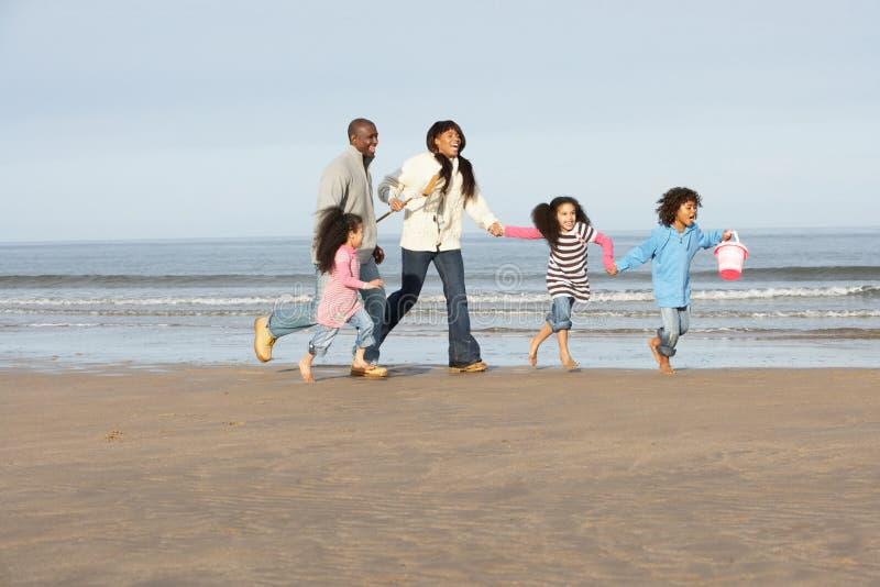 Οικογένεια που τρέχει στη χειμερινή παραλία στοκ φωτογραφία