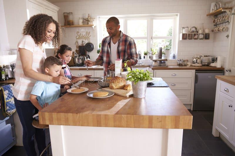 Οικογένεια που τρώει στο σπίτι το πρόγευμα στην κουζίνα από κοινού στοκ φωτογραφίες