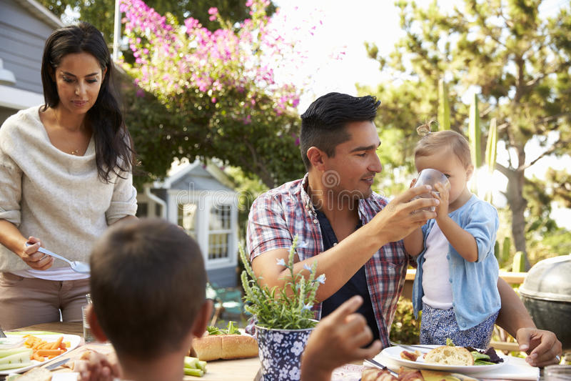 Οικογένεια που τρώει στο σπίτι το υπαίθριο γεύμα στον κήπο από κοινού στοκ φωτογραφίες