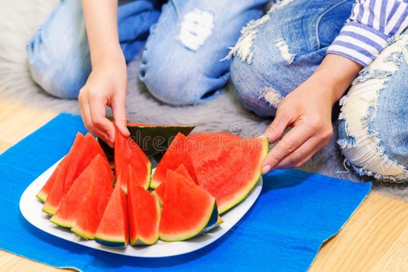 Οικογένεια που τρώει το καρπούζι στο πάτωμα στοκ φωτογραφίες