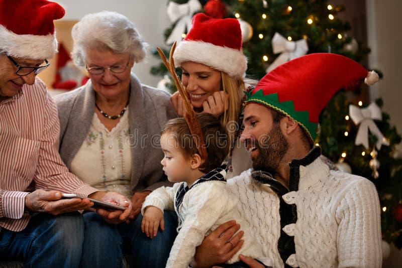 Οικογένεια που φαίνεται φωτογραφίες Χριστουγέννων στο τηλέφωνο κυττάρων στοκ εικόνες