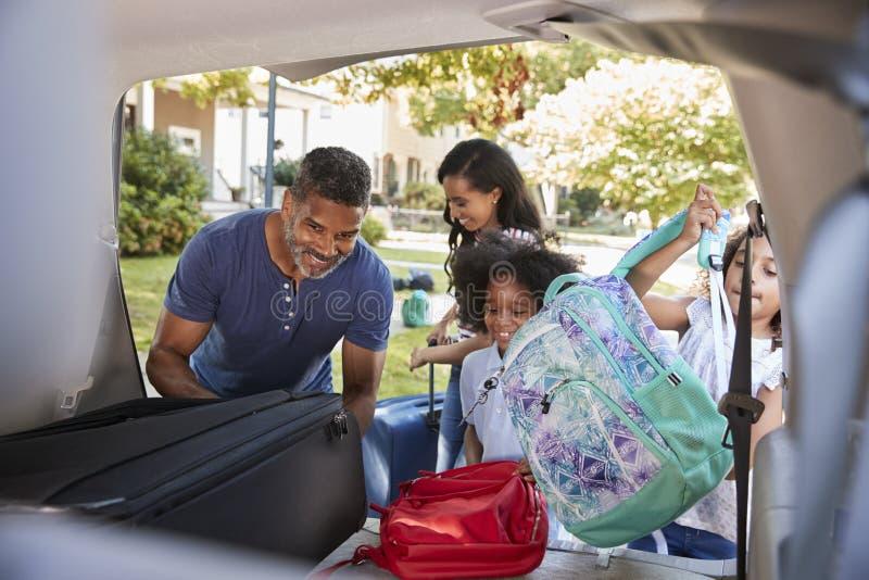 Οικογένεια που φεύγει για τις αποσκευές φόρτωσης διακοπών στο αυτοκίνητο στοκ φωτογραφία με δικαίωμα ελεύθερης χρήσης