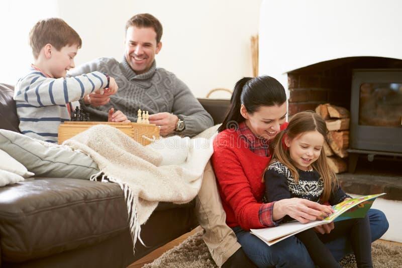 Οικογένεια που χαλαρώνει το σκάκι στο εσωτερικό παιχνιδιού και ανάγνωση του βιβλίου στοκ εικόνα με δικαίωμα ελεύθερης χρήσης