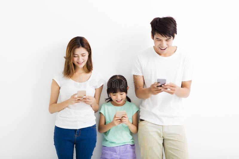 Οικογένεια που χρησιμοποιεί τα έξυπνα τηλέφωνα στεμένος από κοινού στοκ εικόνες