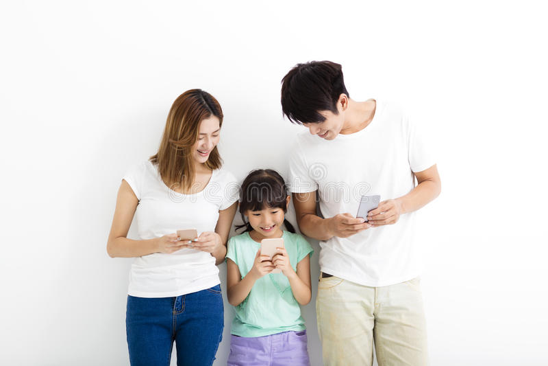 Οικογένεια που χρησιμοποιεί τα έξυπνα τηλέφωνα στεμένος από κοινού στοκ φωτογραφία με δικαίωμα ελεύθερης χρήσης