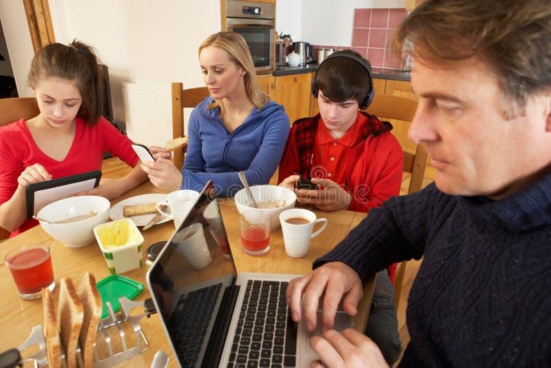 Οικογένεια που χρησιμοποιεί τις συσκευές ταυτόχρονα τρώγοντας το πρόγευμα στοκ φωτογραφία με δικαίωμα ελεύθερης χρήσης
