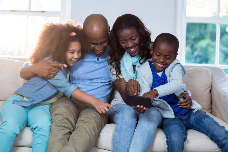 Οικογένεια που χρησιμοποιεί το κινητό τηλέφωνο στοκ φωτογραφία με δικαίωμα ελεύθερης χρήσης
