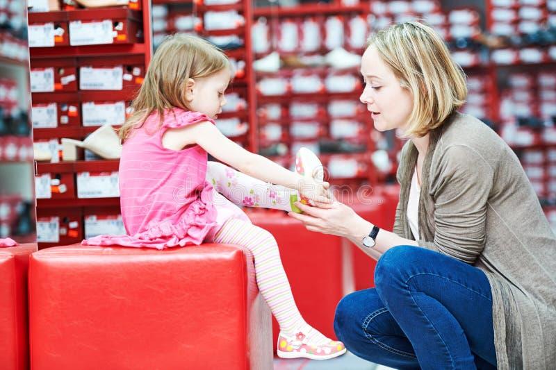 Οικογένεια που ψωνίζει επιλέγοντας τα παπούτσια υποδημάτων παιδιών στοκ εικόνα