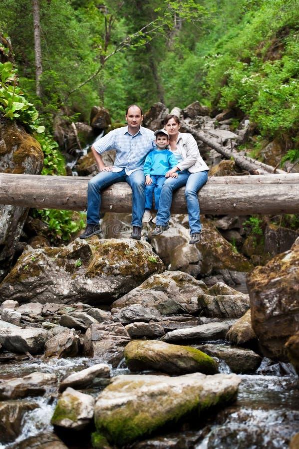 Οικογένεια σε ένα πεσμένο δέντρο πέρα από τον ποταμό στοκ εικόνα