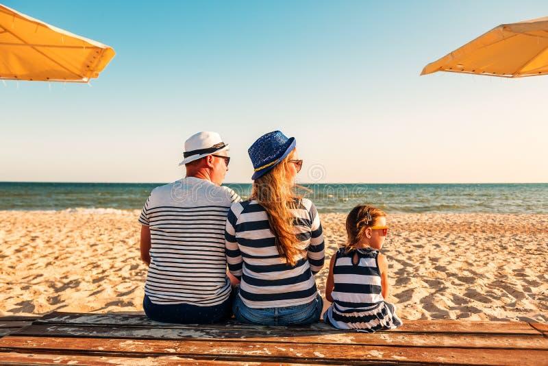 Οικογένεια στα ριγωτά ενδύματα που κάθεται στην παραλία στοκ εικόνες
