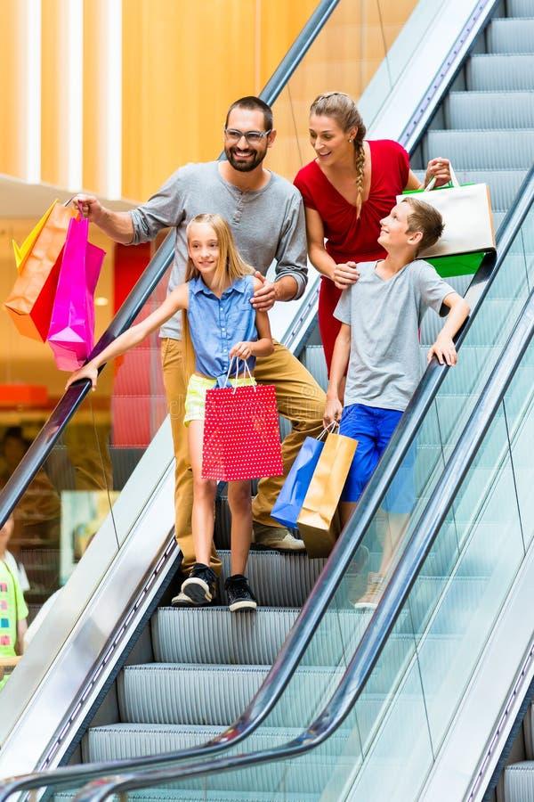 Οικογένεια στη λεωφόρο αγορών στις κυλιόμενες σκάλες στοκ εικόνες με δικαίωμα ελεύθερης χρήσης