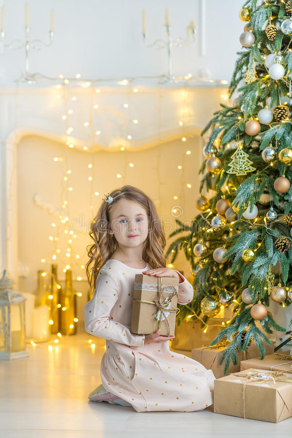 Οικογένεια στη Παραμονή Χριστουγέννων στην εστία Τα παιδιά που ανοίγουν τα Χριστούγεννα παρουσιάζουν Παιδιά κάτω από το χριστουγε στοκ φωτογραφία με δικαίωμα ελεύθερης χρήσης
