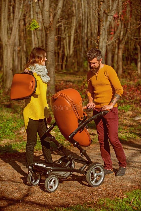 Οικογένεια στον περίπατο ευχαρίστησης στο πάρκο Οικογένεια του περιπάτου πατέρων και μητέρων με το καροτσάκι μωρών υπαίθριο Ξοδεύ στοκ εικόνα