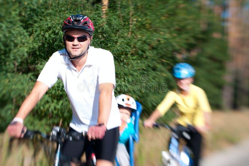 Οικογένεια στο ποδήλατο στον ηλιόλουστο στοκ εικόνες