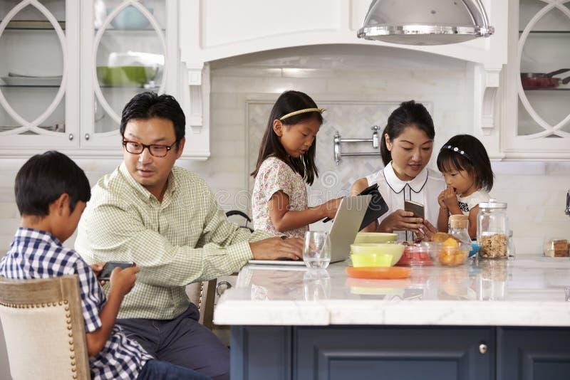 Οικογένεια στο πρόγευμα που χρησιμοποιεί τις ψηφιακές συσκευές στοκ φωτογραφίες