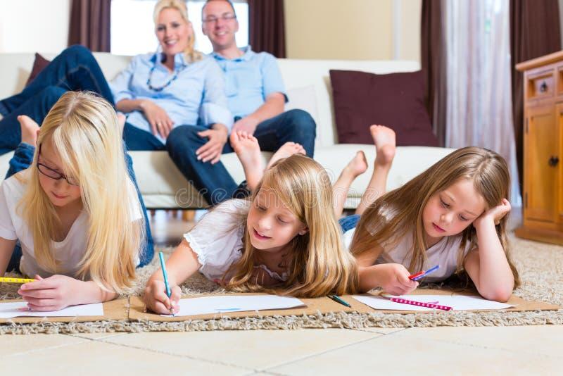 Οικογένεια στο σπίτι, τα παιδιά που χρωματίζουν στο πάτωμα στοκ εικόνα με δικαίωμα ελεύθερης χρήσης
