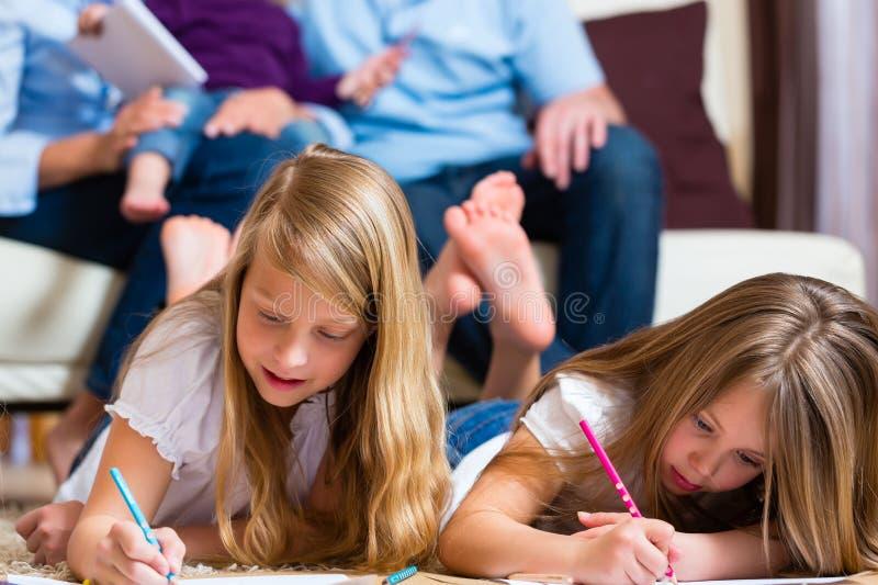 Οικογένεια στο σπίτι, τα παιδιά που χρωματίζουν στο πάτωμα στοκ φωτογραφία