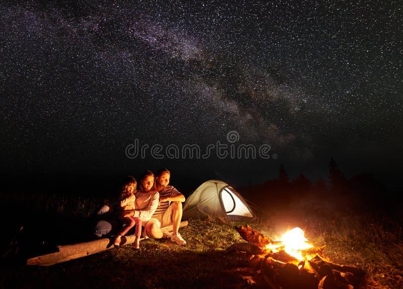Οικογένεια τουριστών με την κόρη που έχει ένα υπόλοιπο στα βουνά τη νύχτα κάτω από τον έναστρο ουρανό με το γαλακτώδη τρόπο στοκ φωτογραφία
