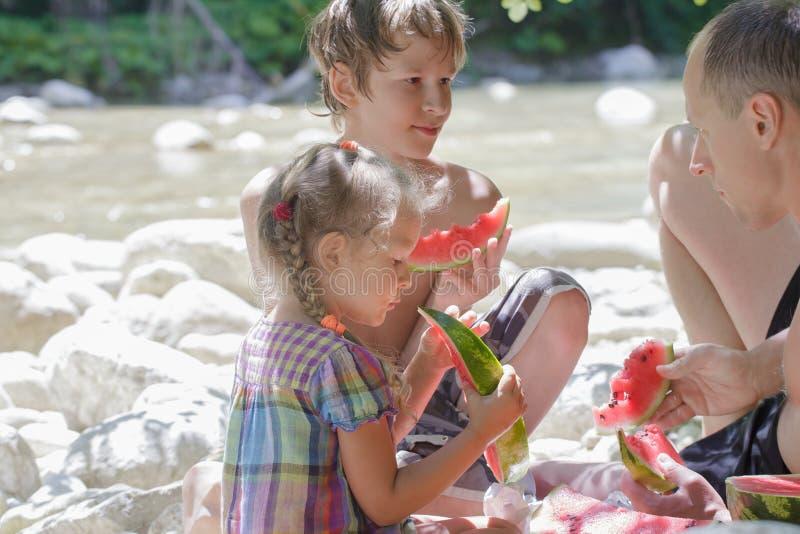 Οικογένεια του πικ-νίκ τριών παραλιών με το καρπούζι στοκ φωτογραφία με δικαίωμα ελεύθερης χρήσης