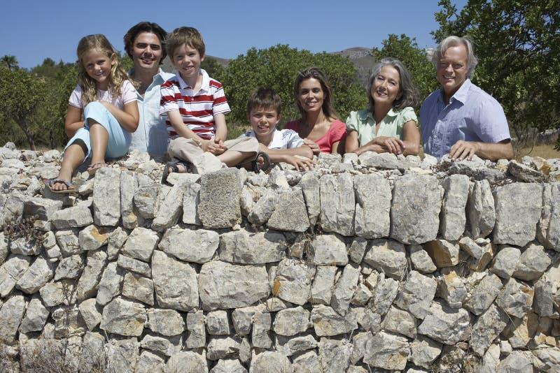 Οικογένεια τριών γενεάς ενάντια στον πέτρινο τοίχο στοκ εικόνες