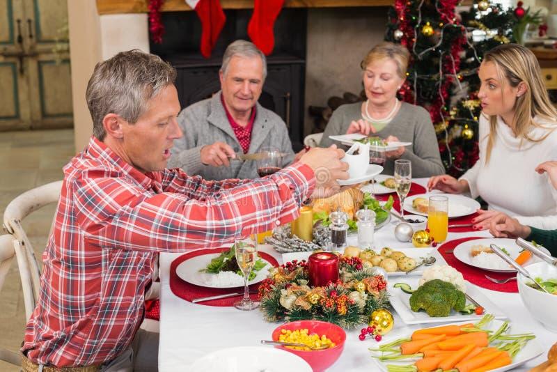 Οικογένεια τριών γενεάς που έχει το γεύμα Χριστουγέννων από κοινού στοκ εικόνες