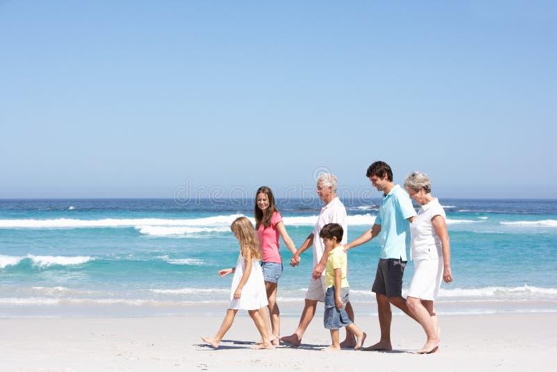 Οικογένεια τριών γενεάς που περπατά κατά μήκος της αμμώδους παραλίας στοκ φωτογραφίες