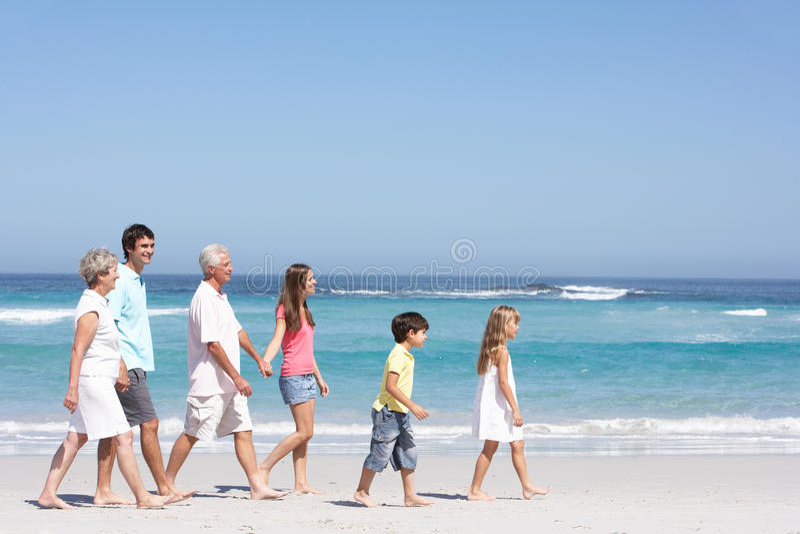 Οικογένεια τριών γενεάς που περπατά κατά μήκος της αμμώδους παραλίας στοκ εικόνες
