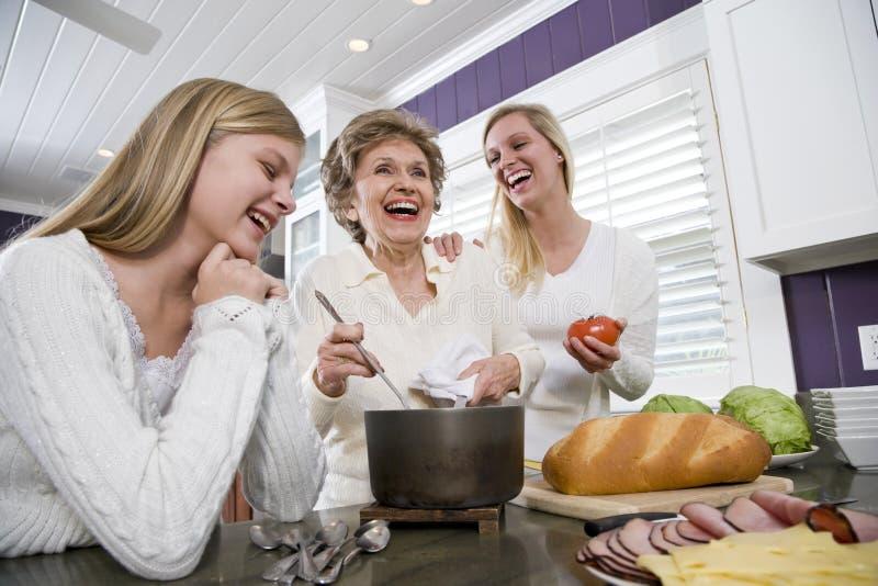 Οικογένεια τριών γενεάς στο μαγειρεύοντας μεσημεριανό γεύμα κουζινών στοκ εικόνες