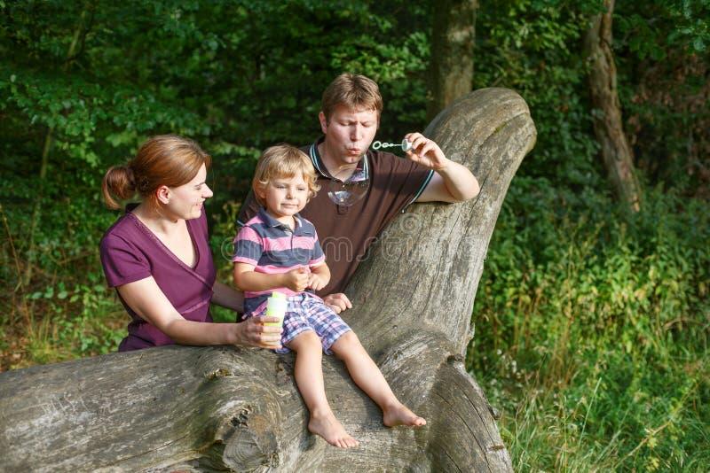 Οικογένεια τριών φυσώντας φυσαλίδων σαπουνιών μαζί στο θερινό δάσος στοκ εικόνες με δικαίωμα ελεύθερης χρήσης