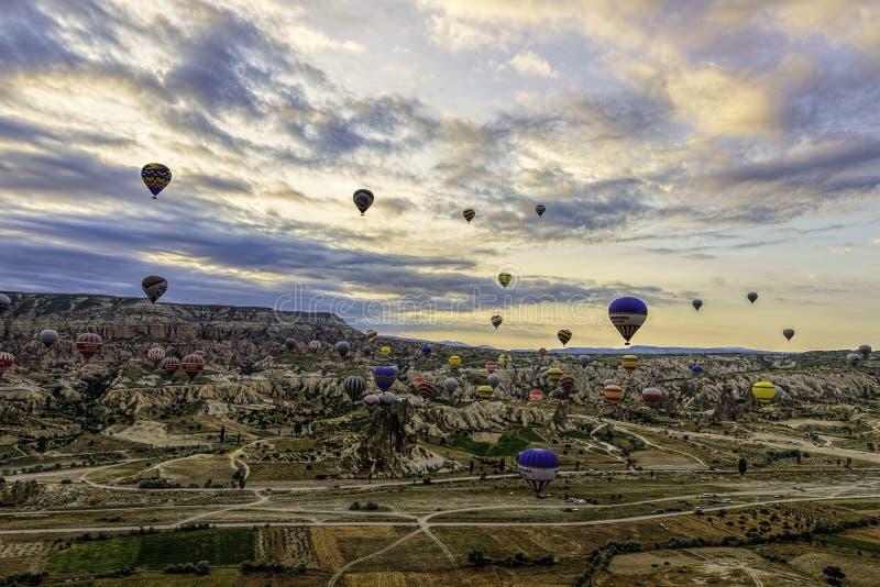 Οικογένεια των καπνοδόχων νεράιδων σε Cappadoccia κάτω από τους νεφελώδεις ουρανούς με τα μπαλόνια ζεστού αέρα στην απόσταση στοκ φωτογραφία με δικαίωμα ελεύθερης χρήσης