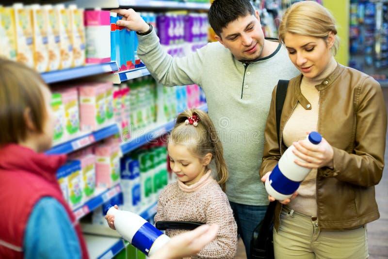 Οικογένεια των πελατών με τα παιδιά που αγοράζουν το γάλα στοκ φωτογραφία με δικαίωμα ελεύθερης χρήσης