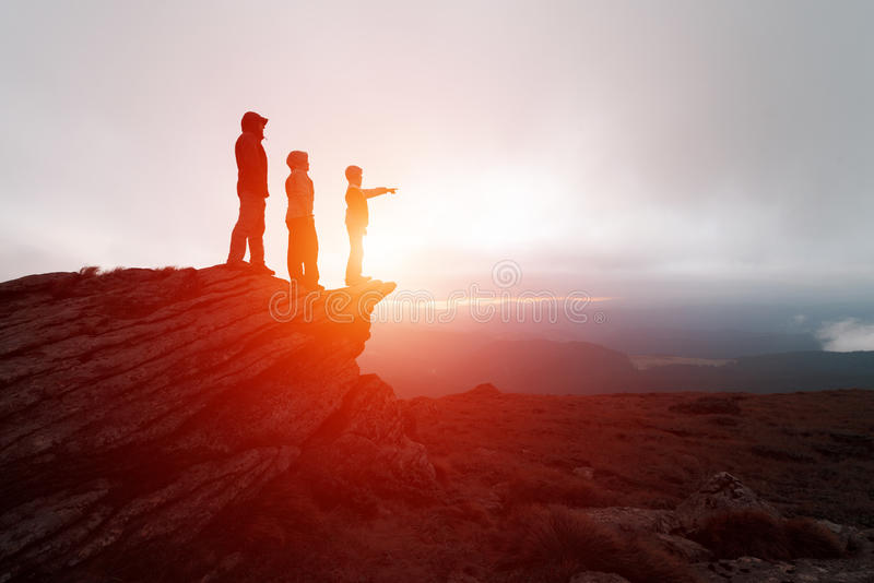 Οικογένεια των τουριστών που μένουν στην άκρη του απότομου βράχου στοκ εικόνα με δικαίωμα ελεύθερης χρήσης