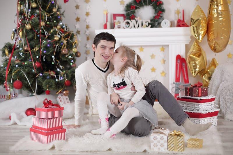 Οικογένεια, Χριστούγεννα, Χριστούγεννα, ευτυχία και έννοια ανθρώπων - χαμογελώντας πατέρας και κιβώτιο δώρων εκμετάλλευσης κορών στοκ εικόνα
