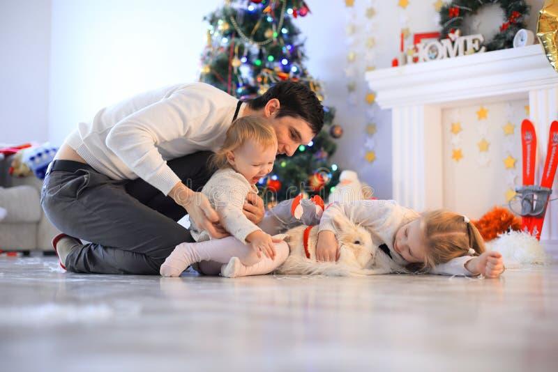 Οικογένεια, Χριστούγεννα, Χριστούγεννα, ευτυχία και έννοια ανθρώπων - χαμογελώντας πατέρας και κιβώτιο δώρων εκμετάλλευσης κορών στοκ φωτογραφία