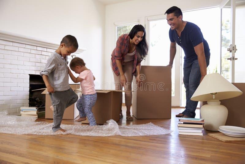 Οικογενειακά ανοίγοντας κιβώτια στο νέο σπίτι στην κίνηση της ημέρας στοκ εικόνες